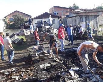 Voluntários limpam o terreno após o incêndio, para a reconstrução
